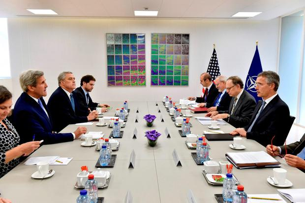 US Secretary of State John Kerry (L) and members of his delegation take their places at the table opposite NATO Secretary General Jens Stoltenberg (R) and his delegation ahead of a meeting at the NATO headquarters in Brussels. Getty Images