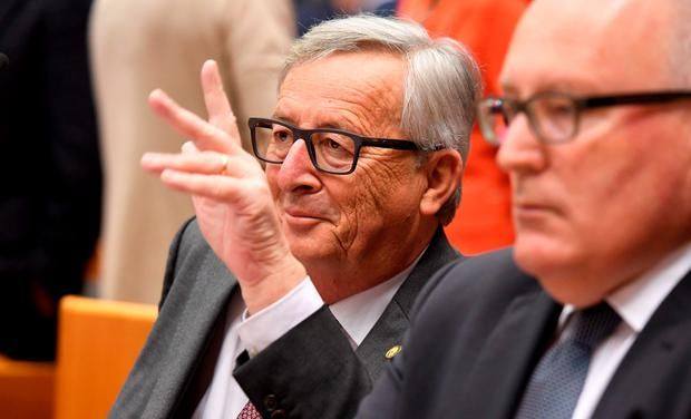 European Commission President Jean-Claude Juncker, left, waves prior to addressing a special session of European Parliament in Brussels on Tuesday, June 28, 2016. (AP Photo/Geert Vanden Wijngaert)