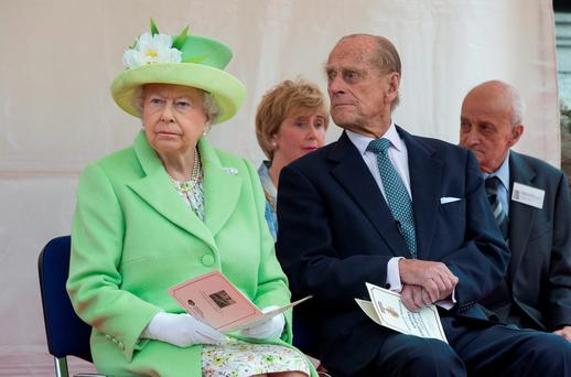 Queen Elizabeth II and the Duke of Edinburgh during a visit to Bushmills Village, where she is unveiling a statue of Robert Quigg, VC, during the second day of her visit to Northern Ireland to mark her 90th birthday. Photo: Carrie Davenport/PA Wire