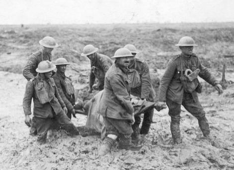 A stretcher party carries a wounded soldier through the mud during the Battle of Passchendaele in Flanders. Photo by John Warwick Brooke/Getty Images