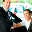 Man buying a car in dealership sitting in his new auto; they are shaking hands to close the deal