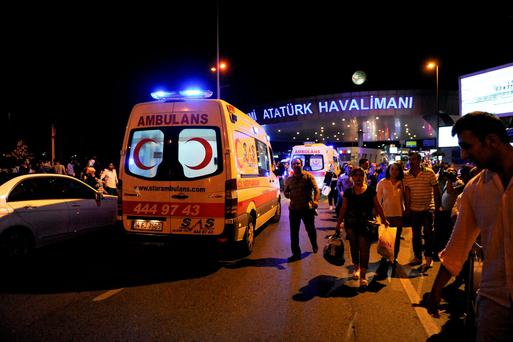 Passengers leave Istanbul Ataturk Airport after a suicide bomb attack. (Photo by Gokhan Tan/Getty Images)