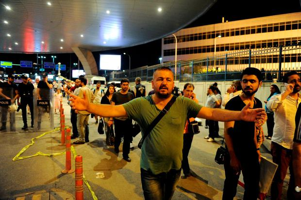 Passengers react as they leave the Istanbul Ataturk Airport. (Photo by Gokhan Tan/Getty Images)