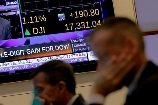 Traders work on the floor as a screen displays the Dow Jones Industrial average just after the opening bell at the New York Stock Exchange