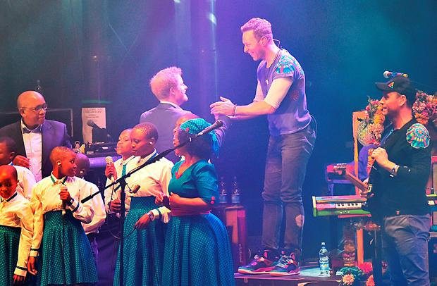 Coldplay's Chris Martin (centre right) shakes hands with Prince Harry during a concert hosted by his charity Sentebale in Kensington Palace Gardens, London, to raise awareness and funds for adolescents living with HIV in sub-Saharan Africa. Credit: Dominic Lipinski/PA Wire