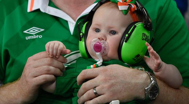 A very young Ireland supporter wears noise protecting headphones and a baby headband in the colors of Ireland prior to the Euro 2016 group E football match between Italy and Ireland / AFP / PHILIPPE LOPEZ
