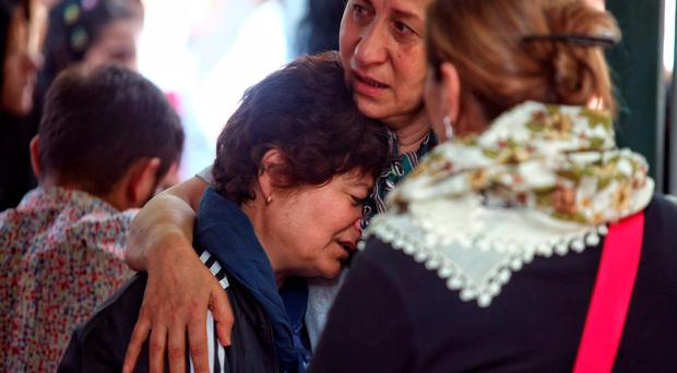 Relatives of 27-year-old flight officer Gulsen Bahadir, a victim of yesterdays attack on Istanbul Ataturk airport, mourn at her Turkish flag-draped coffin during her funeral ceremony in Istanbul. (Photo by Defne Karadeniz/Getty Images)