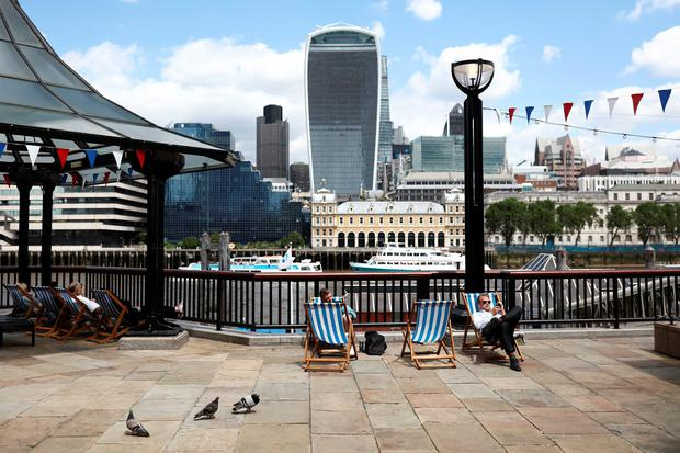 Workers and tourists rest in deckchairs as 20 Fenchurch Street, also known as the 'Walkie-Talkie', centre, stands beyond, in London. Photo: Bloomberg