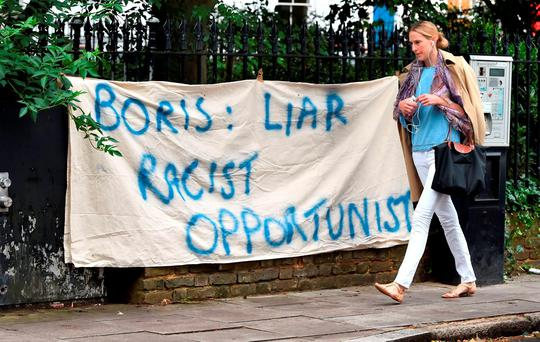A woman walks past a banner put up by protesters opposite the home of Boris Johnson in north London Photo: Dominic Lipinski/PA Wire