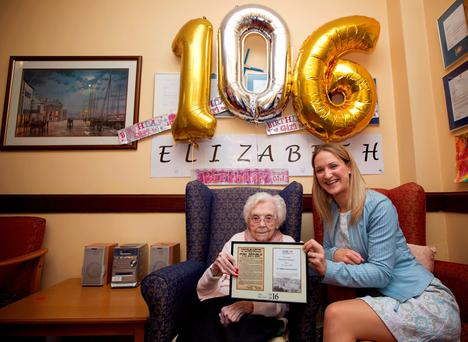 Elizabeth Dempsey is presented with a certificate by Minister for Old People Helen McEntree