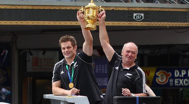 AUCKLAND, NEW ZEALAND - OCTOBER 24: Richie McCaw, (L) the All Black captain and head coach Graham Henry show the world cup to the massed crowds during the New Zealand All Blacks 2011 IRB Rugby World Cup celebration parade on October 24, 2011 in Auckland, New Zealand. The All Blacks won the 2011 RWC Final last night by defeating France 8-7 at Eden Park. (Photo by David Rogers/Getty Images)