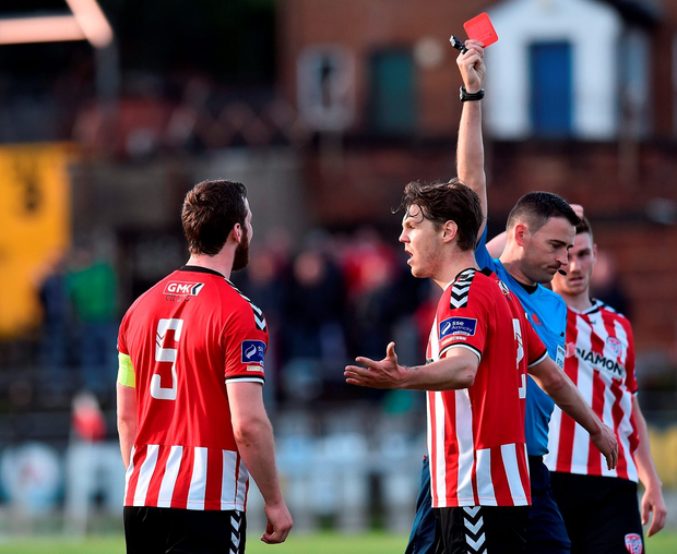 Derry's Ryan McBride, left, is shown the red card by referee Paul McLaughlin. Photo by David Maher/Sportsfile