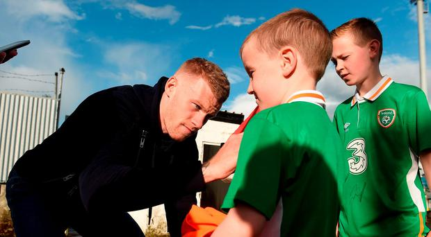 Ireland international and former Derry City player James McClean signs autographs for young supporters before the start of last night's game at the Brandywell. Photo by David Maher/Sportsfile