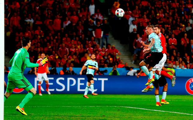 Sam Vokes (1st R) of Wales heads the ball to score his team's third goal past Thibaut Courtois. Photo by Clive Rose/Getty Images