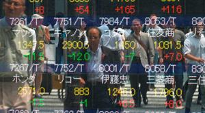 Pedestrians are reflected in the window of a securities company showing stock prices on the Tokyo Stock Exchange. Photo: AFP/Getty Images