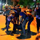 People help an unidentified injured person after a group of gunmen attacked a restaurant popular with foreigners in a diplomatic zone of the Bangladeshi capital Dhaka, Bangladesh. (AP Photo)