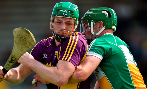 Matthew O'Hanlon of Wexford is tackled by Joe Bergin of Offaly. Photo: Matt Browne/Sportsfile
