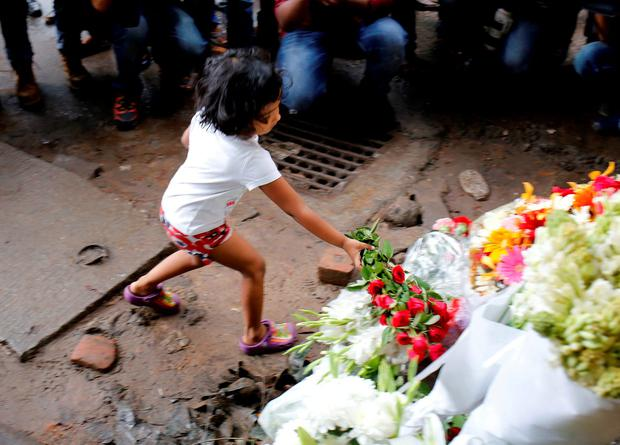 A child places flowers at a makeshift memorial near the site of the killings in Dhaka, Bangladesh. REUTERS/Mohammad Ponir