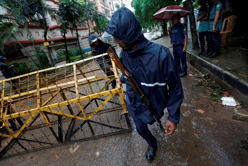 A policeman moves a barricade on the road leading to the Holey Artisan Bakery and the O'Kitchen Restaurant after gunmen attacked, in Dhaka, Bangladesh. REUTERS/Adnan Abidi