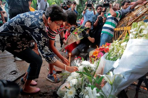 Members of an Indian family offer flowers and light candles as they pay tribute to those killed outside the Holey Artisan Bakery in Dhaka, Bangladesh (AP Photo)