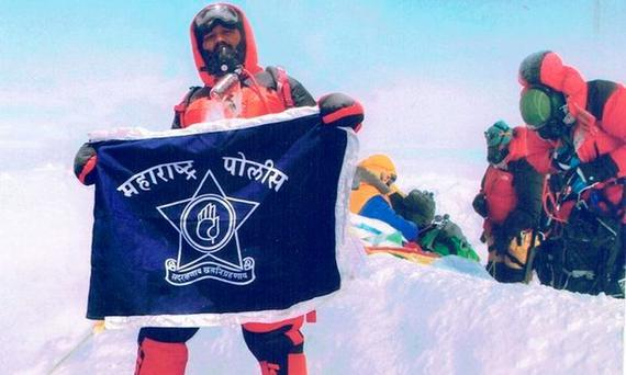 Dinesh Rathod with the Indian flag at what he says is the summit of Mount Everest. Photograph: Facebook