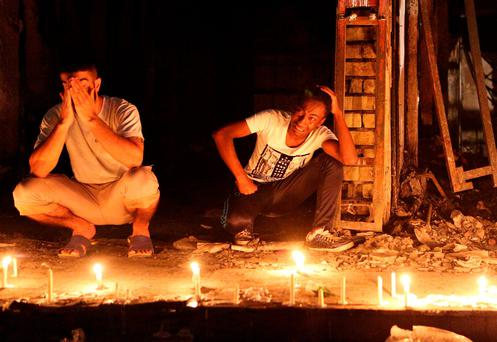 People light candles at the scene of a massive car bomb attack in Karada, a busy shopping district where people were shopping for the upcoming Eid al-Fitr holiday, in the center of Baghdad, Iraq (AP Photo/Hadi Mizban)