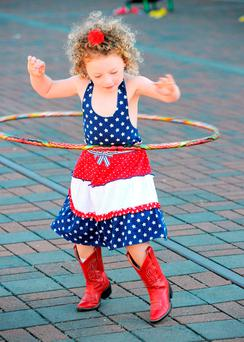 Willow Seixas, 4, of Anacortes works on her hula hoop skills during a city commemoration of veterans and children games at the Anacortes Depot, in Wash., on Sunday (Scott Terrell/Skagit Valley Herald via AP)