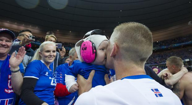Iceland's Ari Freyr Skulason kisses his baby Camilla at the end of the match during the UEFA Euro 2016 Quarter-final match between France and Iceland last summer