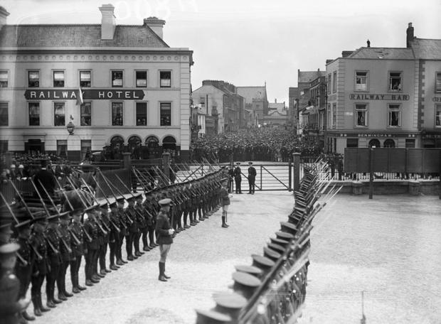 A Guard of Honour by the Railway Hotel and on the adjoining street, huge crowds take up every available standing space. (Part of the Independent Newspapers Ireland/NLI Collection)