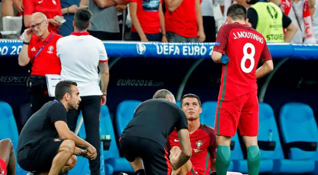 Portugal's Cristiano Ronaldo speaks to Joao Moutinho as he receives treatment before extra time against Poland REUTERS/Christian Hartmann