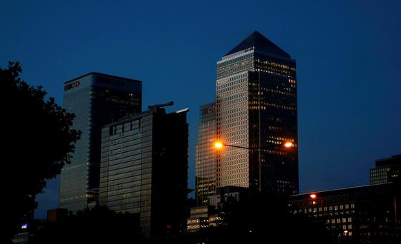 Office lights are on in banks as dawn breaks behind the financial district of Canary Wharf, in London. Photo: Reuters