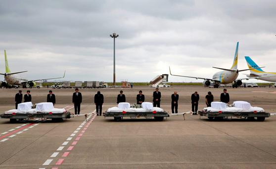 Japanese Foreign Minister Fumio Kishida, third left, with other officials, bows in front of the coffins of the victims who were killed in the last weekend's attack on a restaurant in Bangladeshi capital Dhaka (AP Photo/Shizuo Kambayashi)