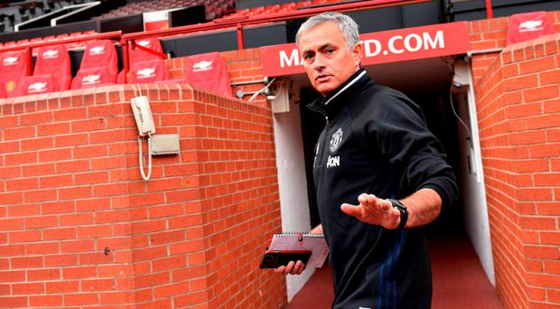 Manchester United's new Portuguese manager Jose Mourinho arrives to pose with a football shirt during a photocall on the pitch at Old Trafford