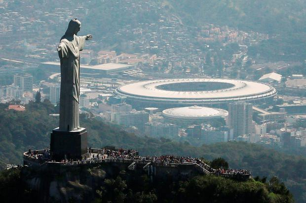 Visitors gather beneath the Christ the Redeemer statue as Maracana stadium, site of the Olympic opening ceremonies, stands in the background. July 5 marks the one-month mark to the beginning of the Rio 2016 Olympic Games with an economic crisis, political turmoil and Zika virus fears roiling the country. (Photo by Mario Tama/Getty Images)