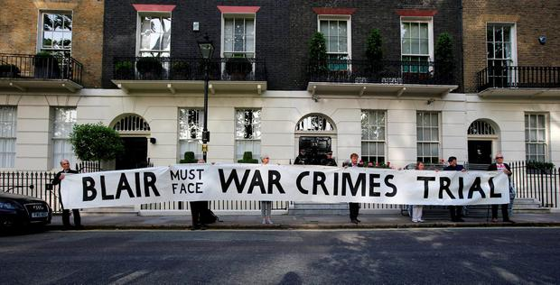 Protesters hold a banner outside the London home of former Prime Minister Tony Blair ahead of the publication of the Chilcot report into the Iraq war. Photo: Jonathan Brady/PA Wire