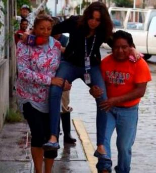'Lady Reportera' - This photo of a journalist being carried through flood water in Puebla, Mexico has gone viral