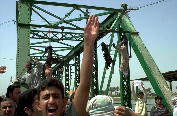 Iraqis chant anti-American slogans as the charred bodies of Westerners dragged from their cars and set alight hang from a bridge over the Tigris river in Fallujah in 2003 Photo: AP Photo/Khalid Mohammed