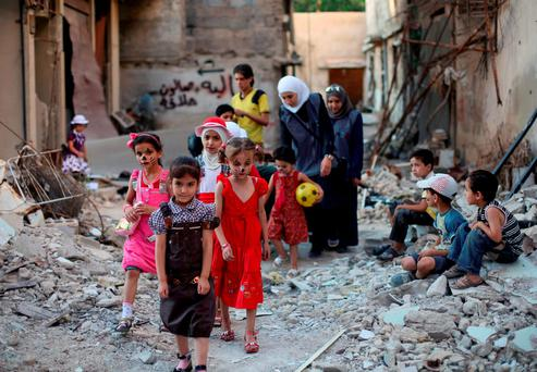 Syrian children walk amidst destruction during an activity organised by a charity group in Jobar, a rebel-held district near Damascus Photo: AMER ALMOHIBANY/AFP/Getty Images