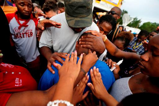 Cameron Sterling, son of Alton Sterling, is comforted by hands from the crowd at a vigil outside the Triple S convenience store in Baton Rouge, La.(AP Photo/Gerald Herbert)