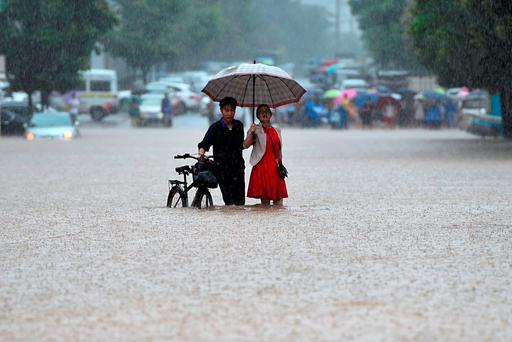A couple holding an umbrella in a rain wade through a flooded road in Wuhan in central China's Hubei province(Chinatopix via AP)