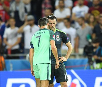 LYON, FRANCE - JULY 6: Gareth Bale (R) of Wales speaks with Cristiano Ronaldo of Portugal after the UEFA Euro 2016 semi final match between Portugal and Wales at Stade de Lyon in Lyon, France on July 6, 2016. (Photo by Mustafa Yalcin/Anadolu Agency/Getty Images)