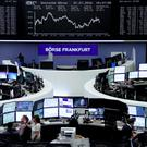 Traders are pictured at their desks in front of the DAX board at the stock exchange in Frankfurt