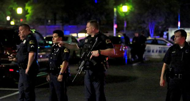 Dallas police stand watch near the scene where four Dallas police officers were shot