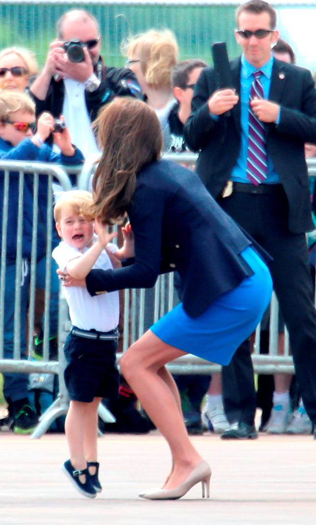 The Duchess of Cambridge picks up Prince George during a visit to the Royal International Air Tattoo at RAF Fairford - the world's largest military airshow