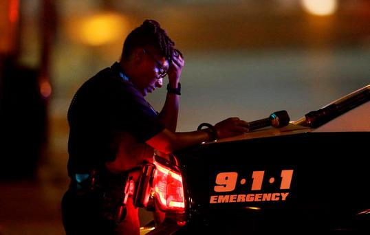 A Dallas police officer, who did not want to be identified, takes a moment as she guards an intersection in the early morning after a shooting in downtown Dallas. (AP Photo/LM Otero)