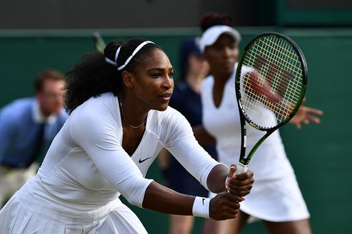 US player Serena Williams (L) and US player Venus Williams (R) play against Russia's Ekaterina Makarova and Elena Vesnina during their women's doubles quarter-final match on the eleventh day of the 2016 Wimbledon Championships at The All England Lawn Tennis Club in Wimbledon, southwest London, on July 7, 2016. / AFP / LEON NEAL / RESTRICTED TO EDITORIAL USE (Photo credit should read LEON NEAL/AFP/Getty Images)