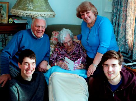 Gladys Hooper looking at a birthday card ahead of her112th birthday surrounded by three generations of her family, son Derek (top left), granddaughter Christine (top right) and great-grandsons Matthew (front left) and David (front right) Credit: Steve Parsons/PA Wire