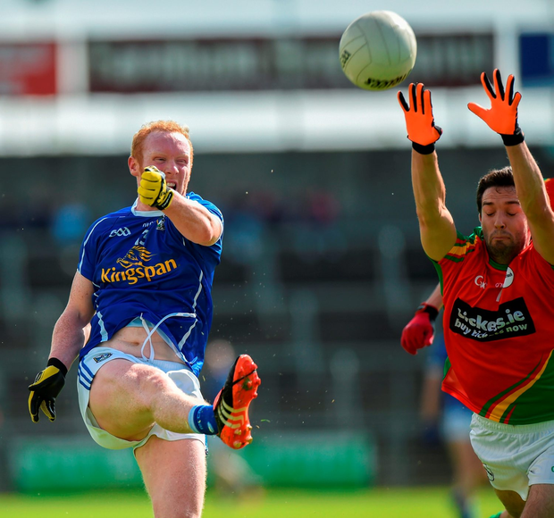 Cian Mackey takes a kick despite the attentions of Brendan Kavanagh. Photo by Matt Browne/Sportsfile