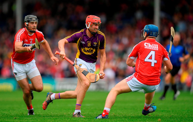 Wexford's Paul Morris tries to take the ball past Cork's Christopher Joyce, left, and Conor O'Sullivan. Photo by Stephen McCarthy/Sportsfile