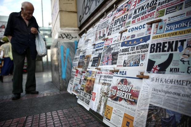 A man browses through newspapers at a kiosk in Athens post-Brexit